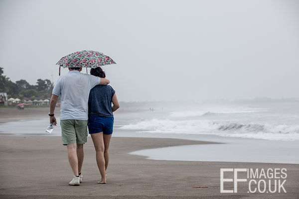 Couple With Umbrella Walking On A Bali Beach In The Rain
