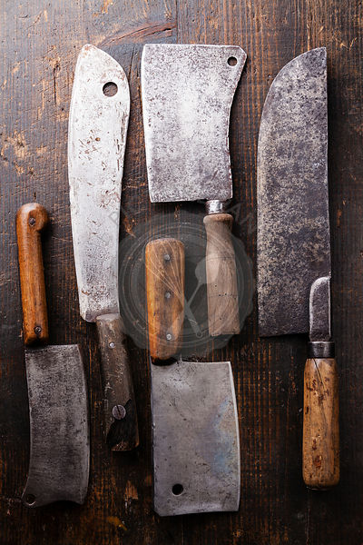 Vintage Butcher meat cleavers on dark wooden background