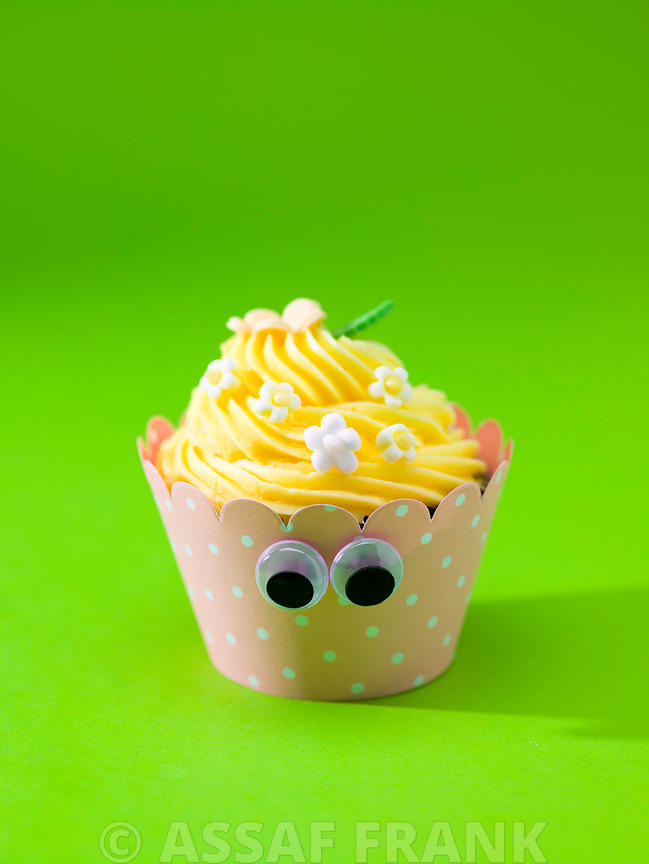 Beautifully decorated cupcake on green background