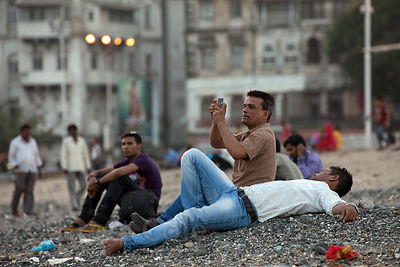Men relax and chat on a weekend Chowpatty Beach, Mumbai, India.
