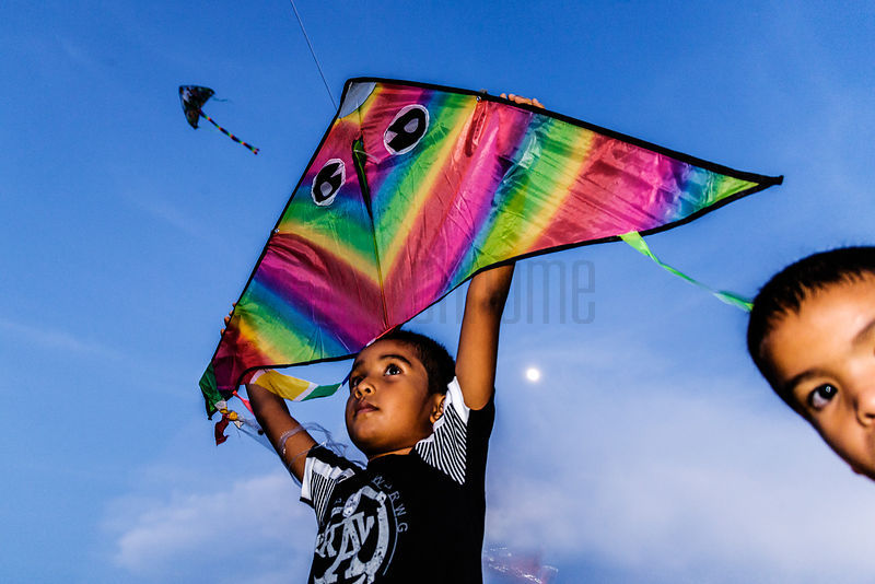 Young Boy Flying a Kite at Dusk