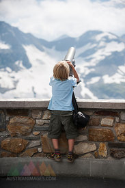 Austria, Grossglockner, Young boy watching through a binocular