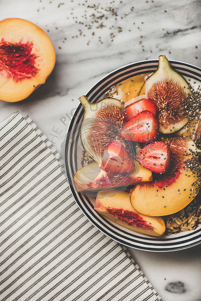 Healthy breakfast bowl with yogurt, fruits and honey, top view