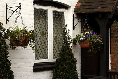 Old White Cottage With Hanging Baskets and Leaded Windows
