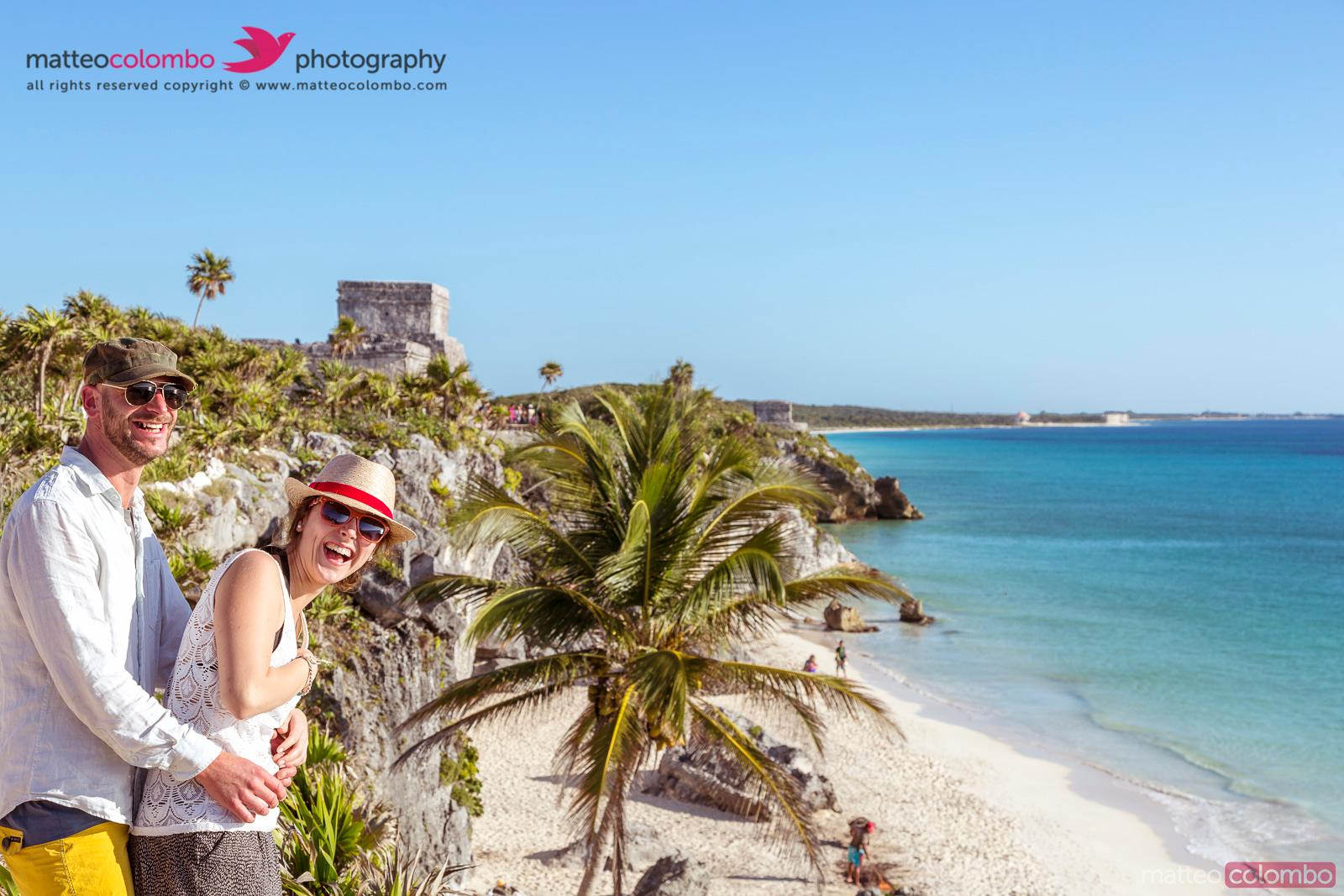 Tourist couple visiting the mayan ruins of Tulum, Mexico