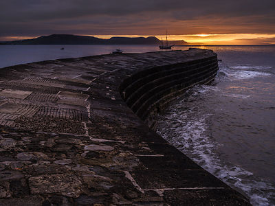 Moody sunrise with Irene anchored off The Cobb in Lyme Regis, Dorset, UK