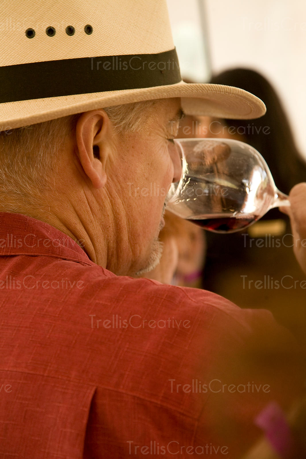 A man in a hat smells the aromas in a glass of red wine