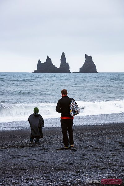 Man and child on a black sand beach, Vik, Iceland