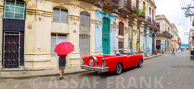 Woman with red umbrella by a vintage car on the street of Havana, Cuba