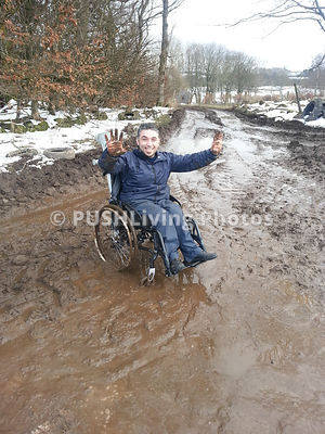 Young man in a wheelchair making hard work of a muddy country lane in winter