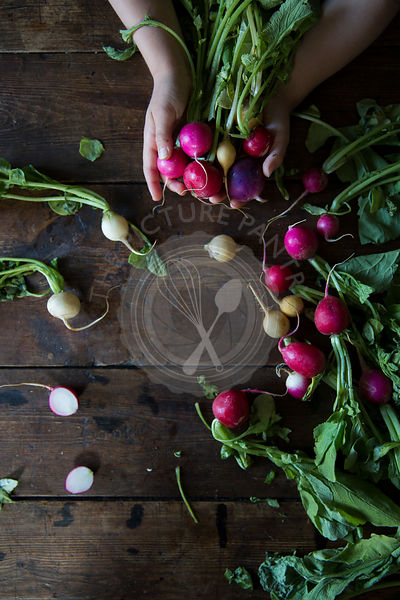 Hands holding a collection of radishes over a wooden board