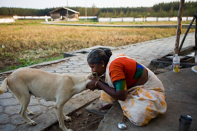 India - Cuddalore - Meena, 65, an elderly resident,  makes a fuss of one of the villages two dogs.s