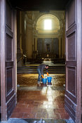 A man carries two buckets of water after scrubbing the floors of a church in Naples