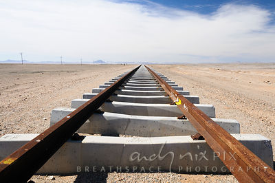 A flat straight section of railway tracks, resting on new concrete railway sleepers, disapearing into the desert in the distance