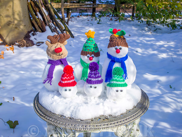 Cute little Christmas snowmen on table covered with snow