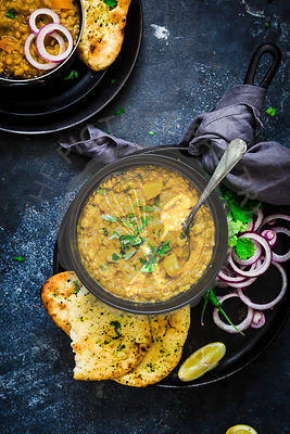 Indian Dahl served with Naan bread, onion rings, lemon wedge and coriander leaves