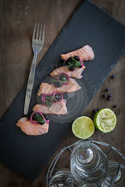 Salmon ceviche with blueberry salsa on slate board and wooden background