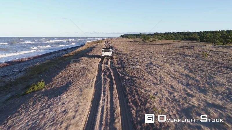 Aerial drone tracking shot of vintage 4x4 off road vehicle driving on a sandy beach Latvia