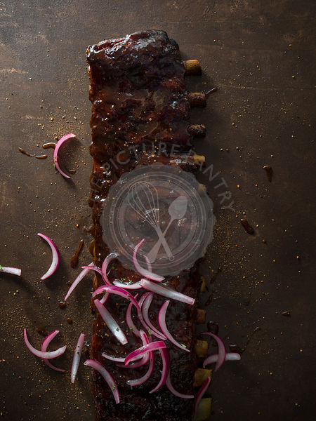 A long rack of ribs sauced with red onion spread over it and spices scattered around thes surface.
