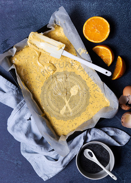Orange poppy seed cake batter in tin with oranges and a bowl of poppy seeds.