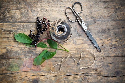 Elderberry juice, elderberries and scissors on a wooden table