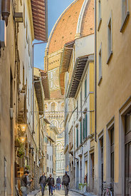 FLORENCE, ITALY - OCTOBER 28, 2018: An old narrow street in the center of Florence, Italy with duomo dome in background