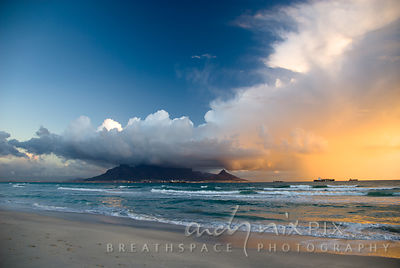 Cumulonimbus cloud over Table Mountain, setting sun illuminating underside of cloud and Lion's Head, four container ships in ...