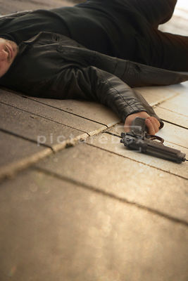 An atmospheric image of a mystery man with a gun laying unconscious on a pavement.