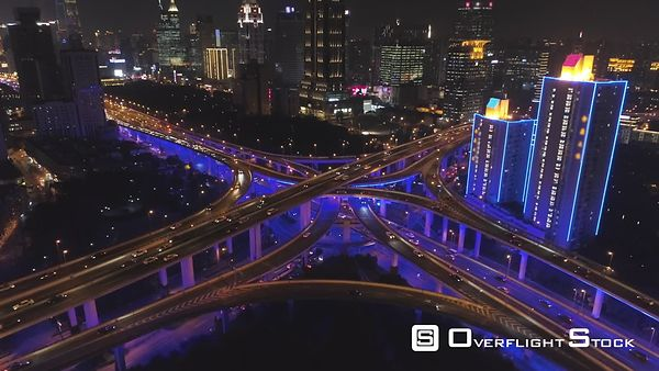 Elevated Road Overpass at Night with Blue Illumination. Shanghai, China. Aerial View. Drone is Flying Forward, Camera is Tilt...