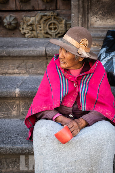 Elderly Peruvian woman holding a cup for donations.