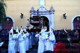 Penitents carrying the Holy Sepulchre out of La Merced church at start of Good Friday procession, La Paz, Bolivia