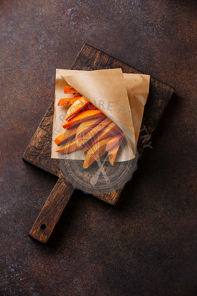 Sweet potato wedges for garnish on wooden cutting board on brown background