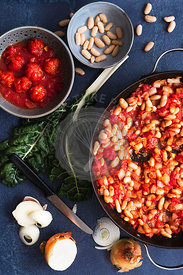 Tomatoes, onions and cannellini beans in a pan beside silverbeet, tomaotoes and sliced onions.