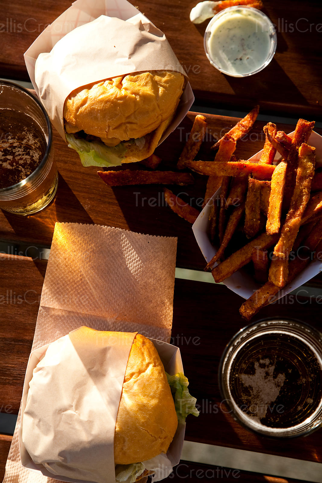 Close-up of grilled cheeseburgers, sweet potato french fries and pints of beer on patio table waiting to be eaten