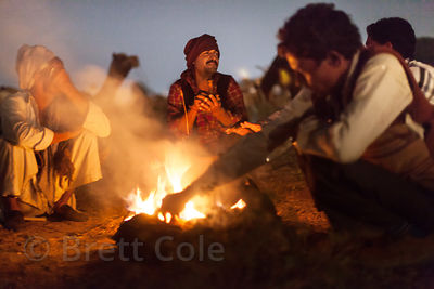 Camel herders chat around a campfire at the Pushkar Camel Mela, Pushkar, Rajasthan, India.