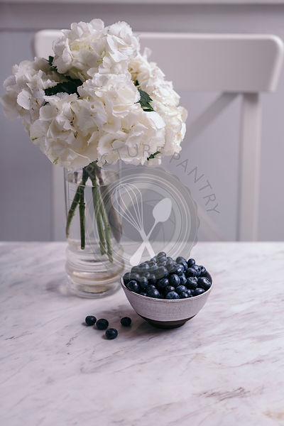 Fresh blueberries in a small white ceramic bowl