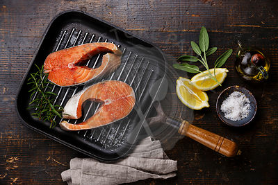Raw salmon Steak on grill pan on wooden background with seasoning