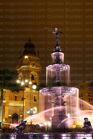 Fountain and tower of cathedral at night, Plaza de Armas, Lima, Peru