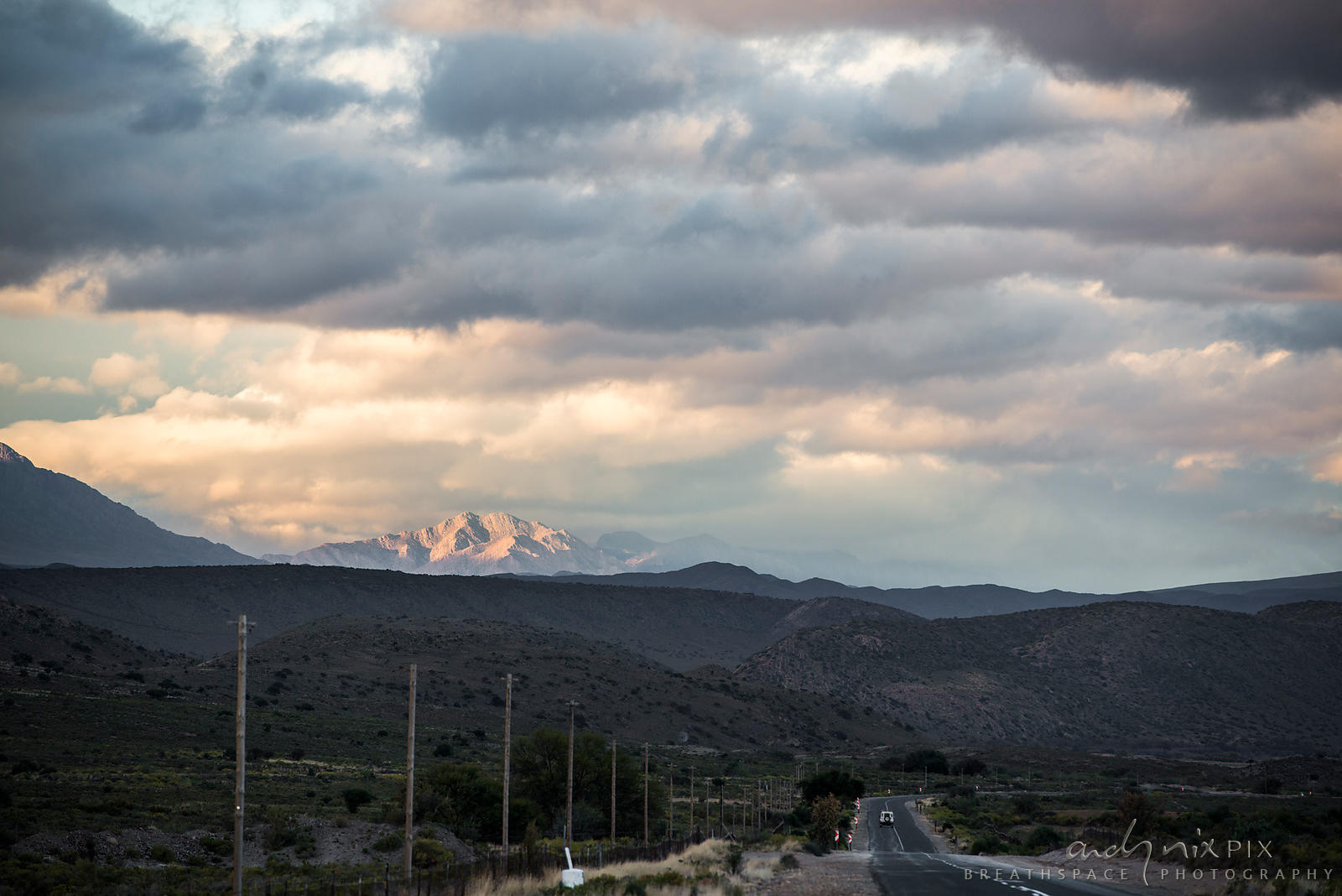 Sunlight on mountain in distance, car on road in foreground, cloudy sky at sunset