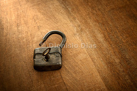 Antique padlock open and with the key on a wooden background