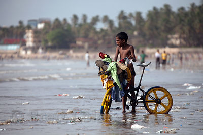 A boy rides his bike along a trash-strewn stretch of Juhu Beach, Mumbai, India.