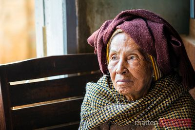 Old woman looking out of the window, Myanmar