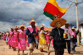 Achu (masked old man figure) leads dance group during main procession of festival, San Ignacio de Moxos, Bolivia