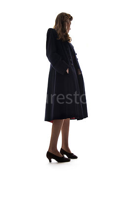 A semi-silhouette of a 1940's woman in a coat – shot from low-level.