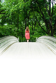An atmospheric image of a girl walking over a bridge in Central Park, New York City.