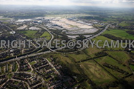Manchester high level aerial view of M56 motorway junction 5 exit for Manchester Airport with farmland in fore ground and Man...