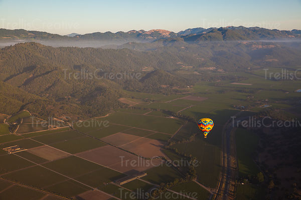 Hot air balloon drifting over a country road in Napa Valley, California