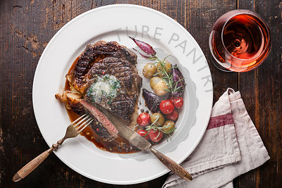 Sliced medium rare grilled Beef steak Ribeye with herb butter and baby potatoes and wine on white plate on wooden background