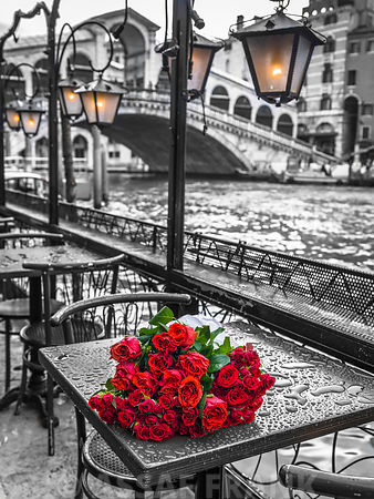Bunch of red roses on street cafe table, Rialto Bridge, Venice, Italy