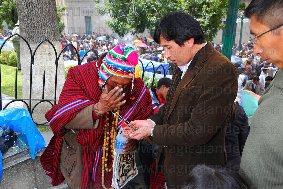 A yatiri or shaman recites prayers as he blesses a client, Alasitas festival, La Paz, Bolivia